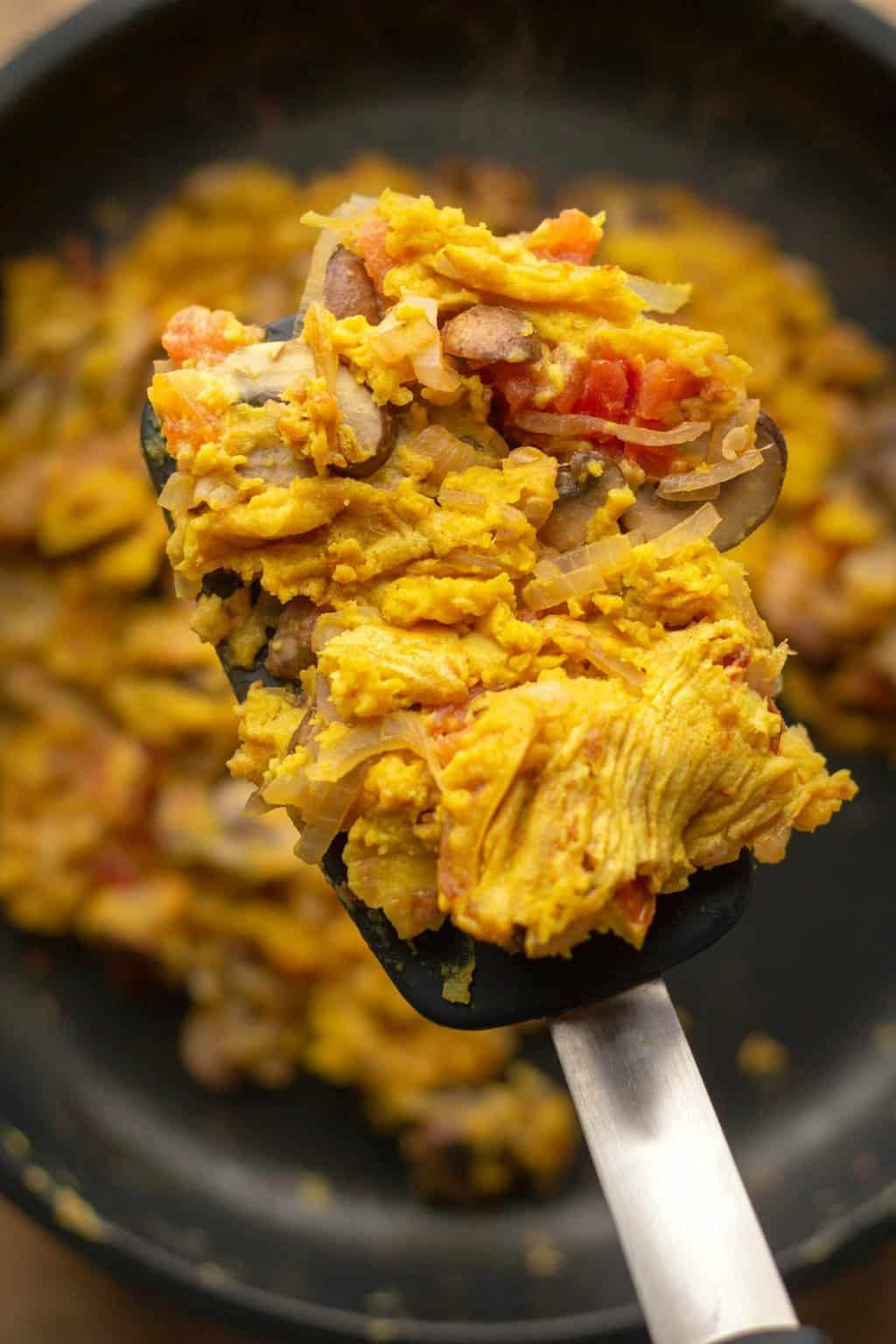Vegan scrambled eggs in a frying pan with a spatula.