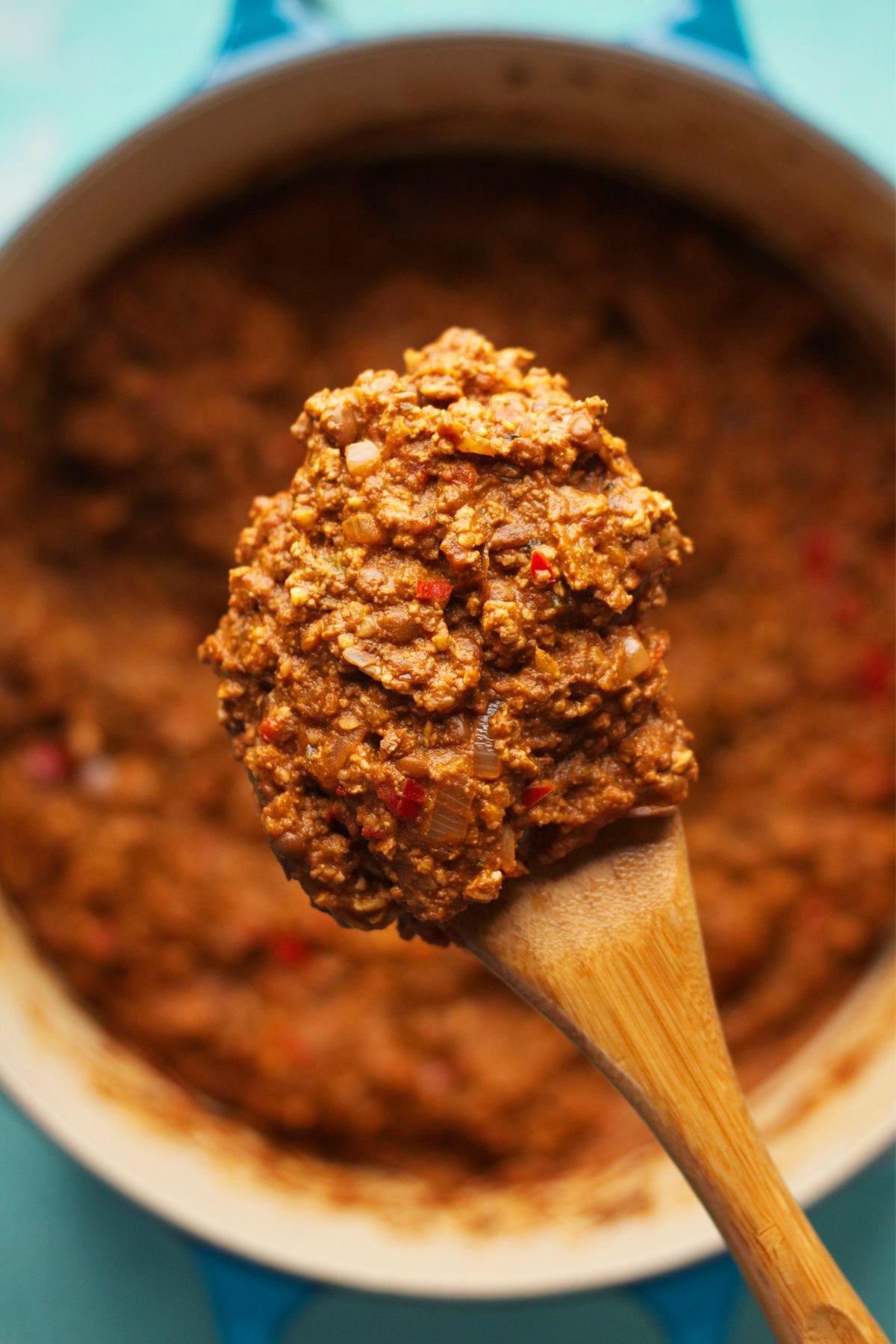 Vegan sloppy joe mince in a pot with a wooden spoon.