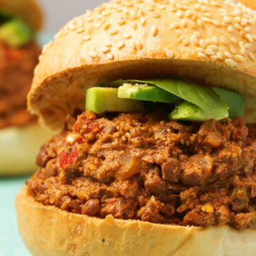 Vegan sloppy joes topped with avocado slices and fresh basil.