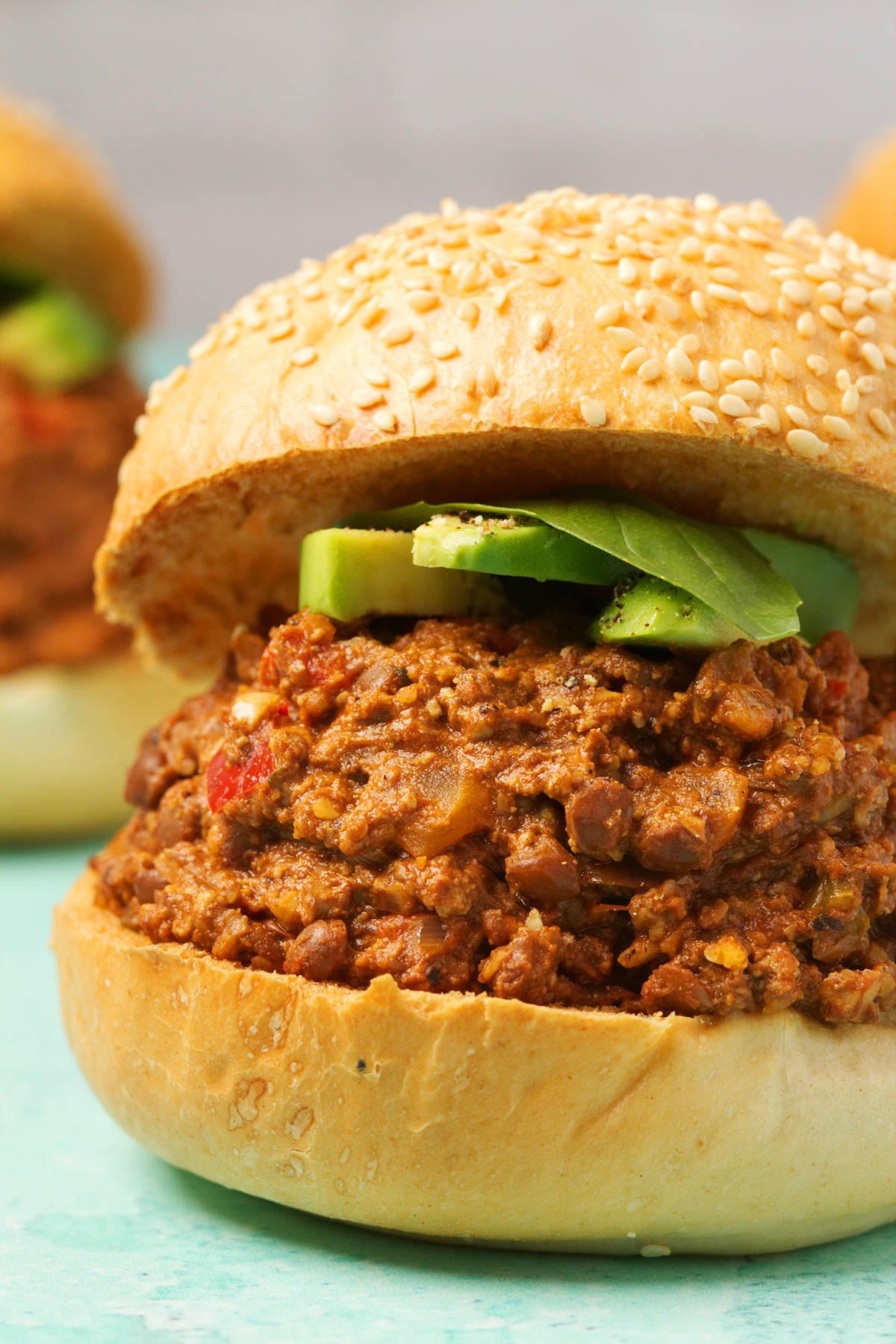 Vegan Sloppy Joe topped with sliced avocado and fresh basil leaves.