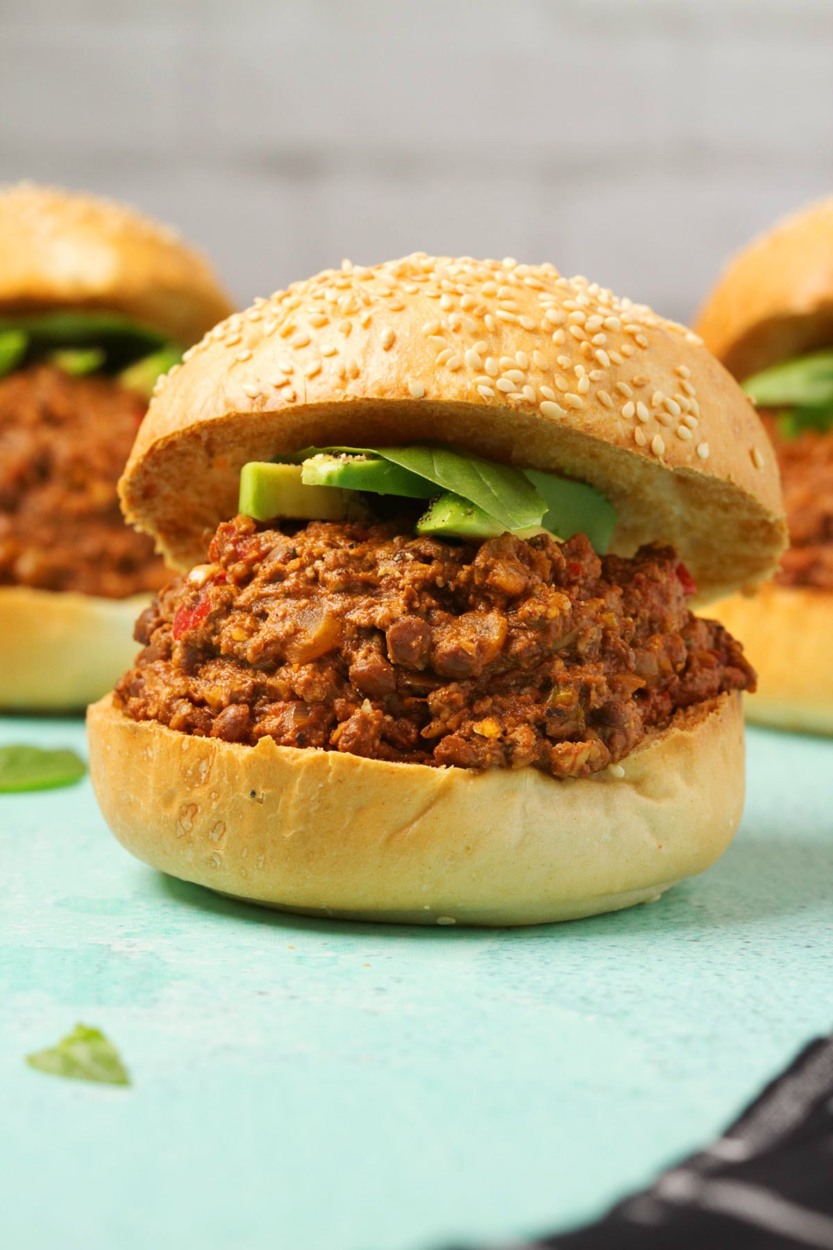 Vegan Sloppy Joe with homemade vegan mince and topped with sliced avocado and fresh basil leaves.