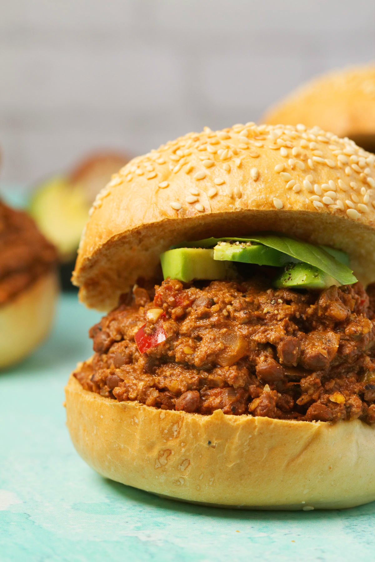Vegan Sloppy Joe topped with sliced avocado and fresh basil.