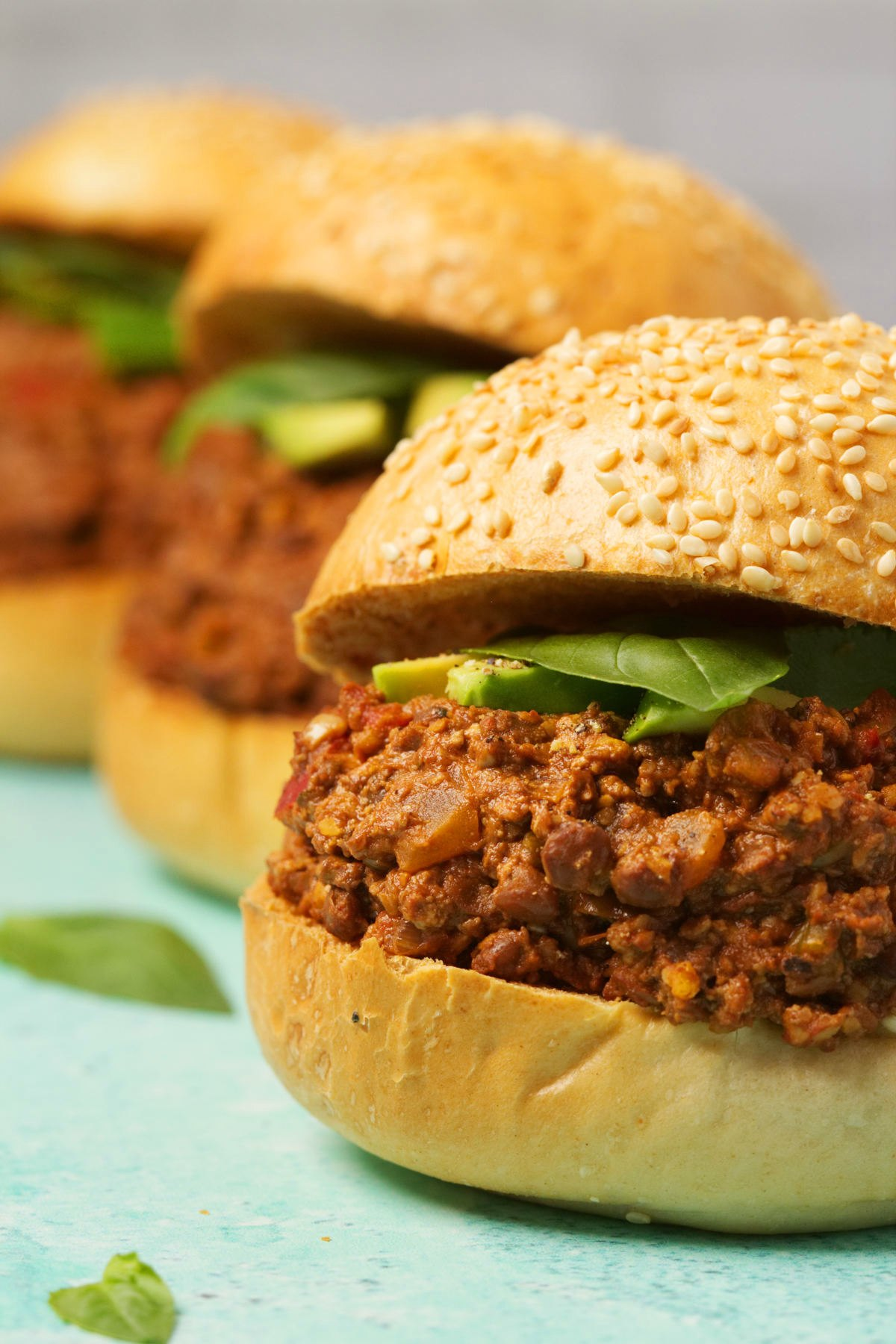 Vegan Sloppy Joes topped with sliced avocado and fresh basil.