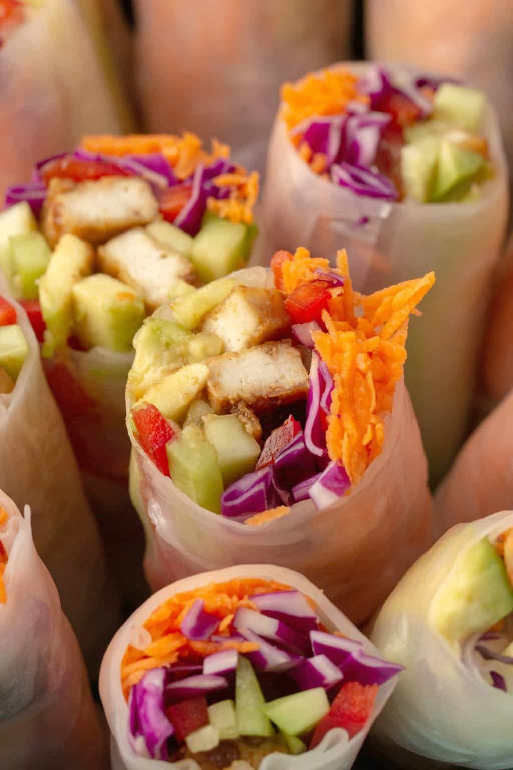 Vegan spring rolls with tofu and veggies standing upright in a black bowl.