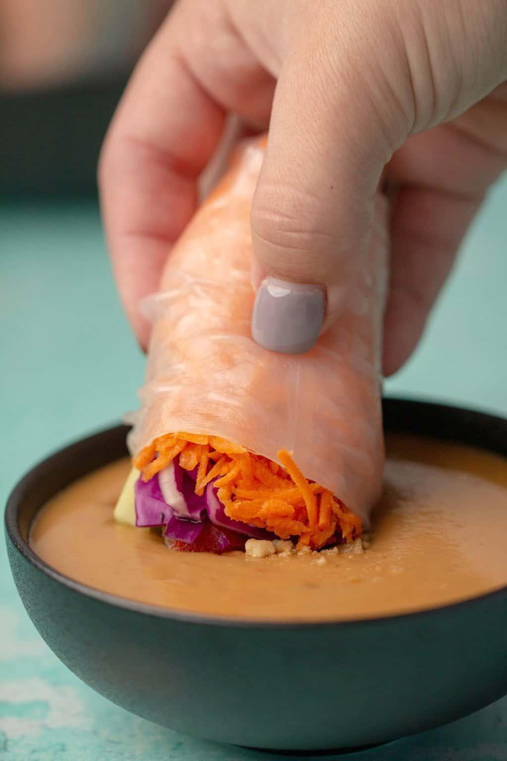 Vegan spring roll dipping into a bowl of vegan peanut sauce.