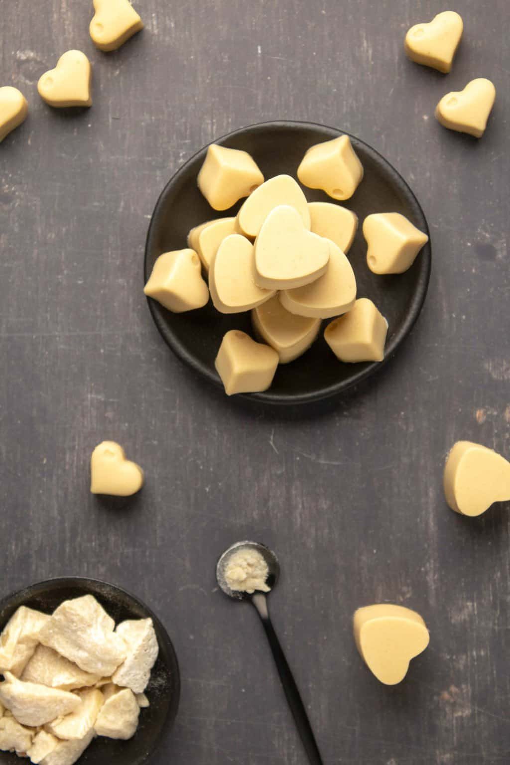 Heart shaped vegan white chocolate stacked up on a black plate.