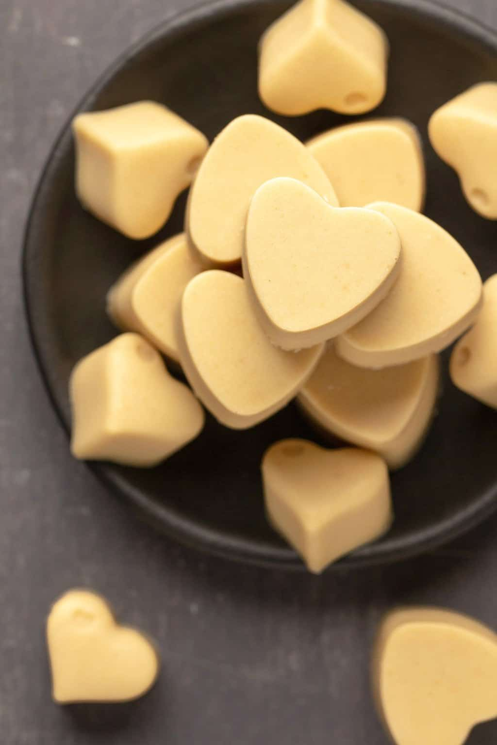 Heart shaped vegan white chocolates stacked up on a black plate.