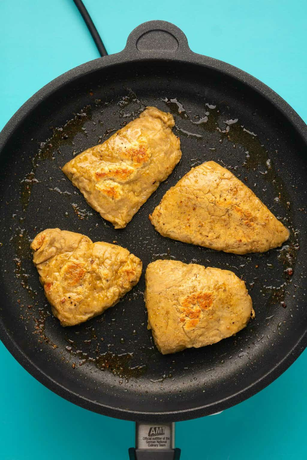 Vegan chicken fillets frying in a frying pan.