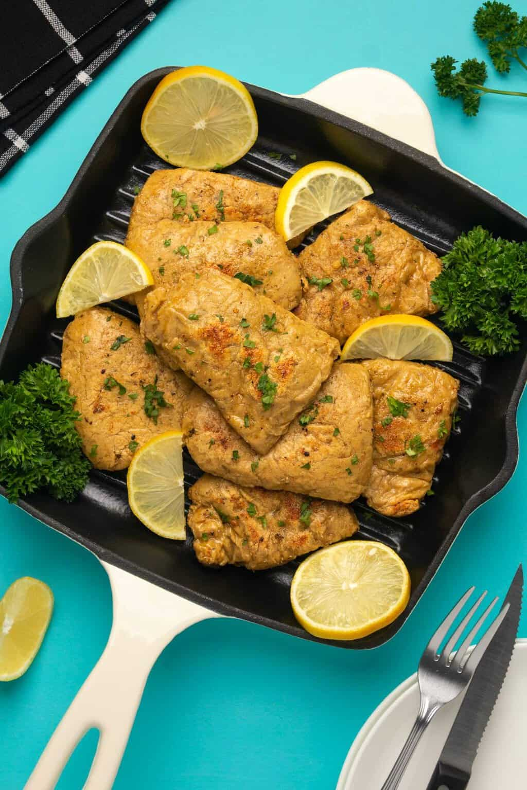 Vegan chicken fillets with fresh parsley and lemon slices in a frying pan.