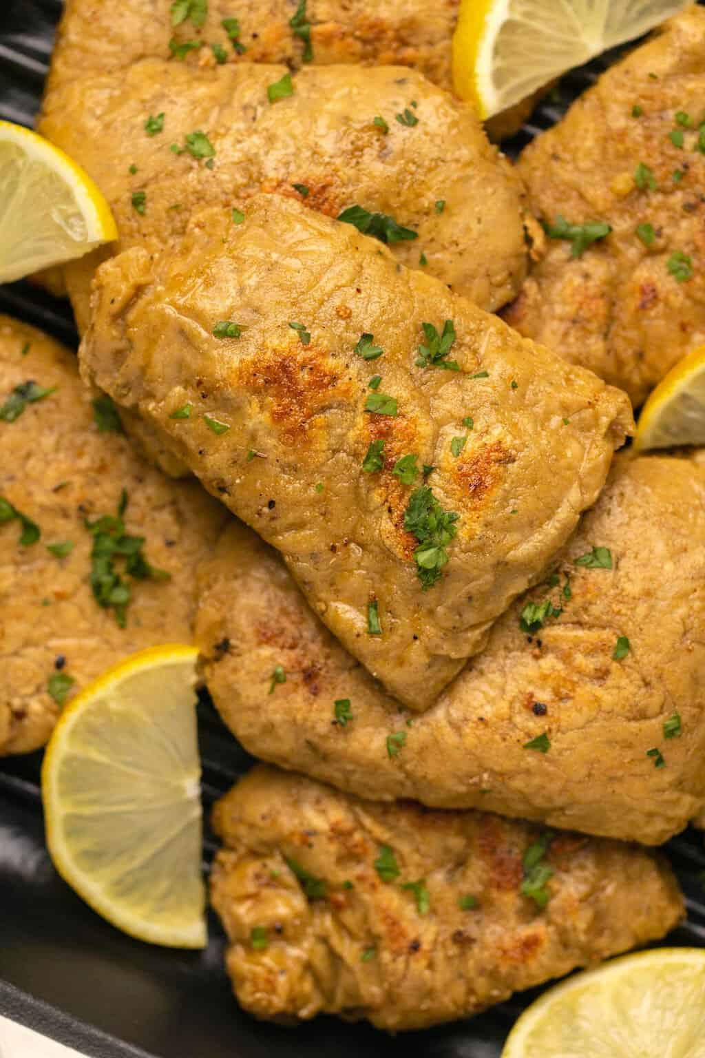 Vegan chicken fillets topped with chopped parsley and lemon slices.