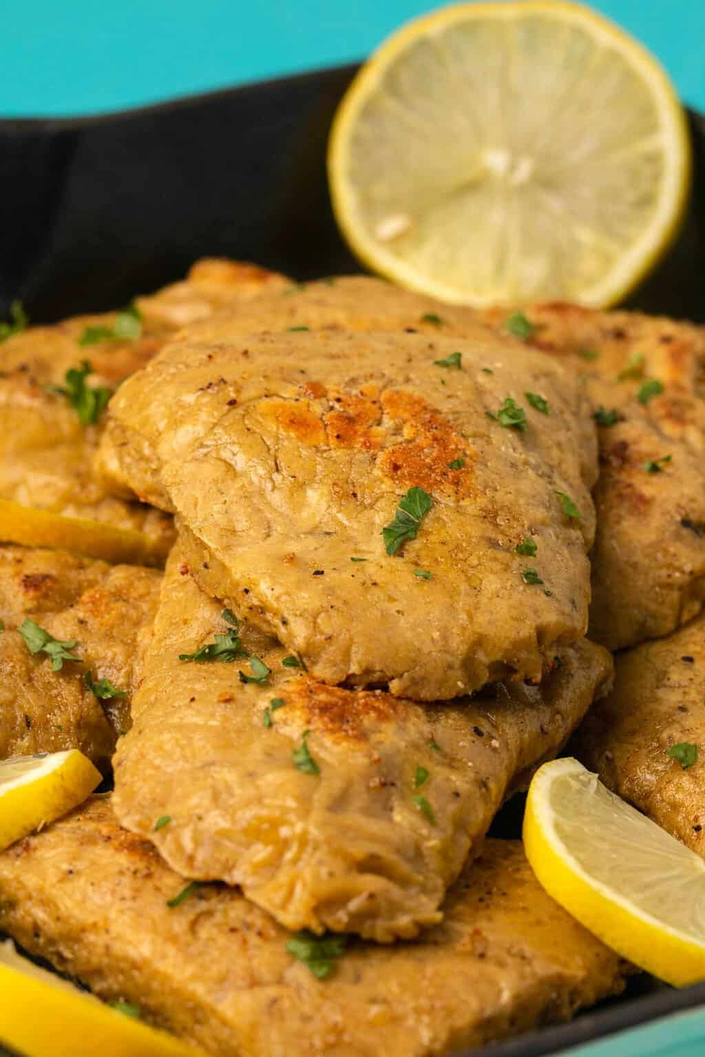 Vegan chicken fillets topped with chopped parsley and fresh lemon slices.
