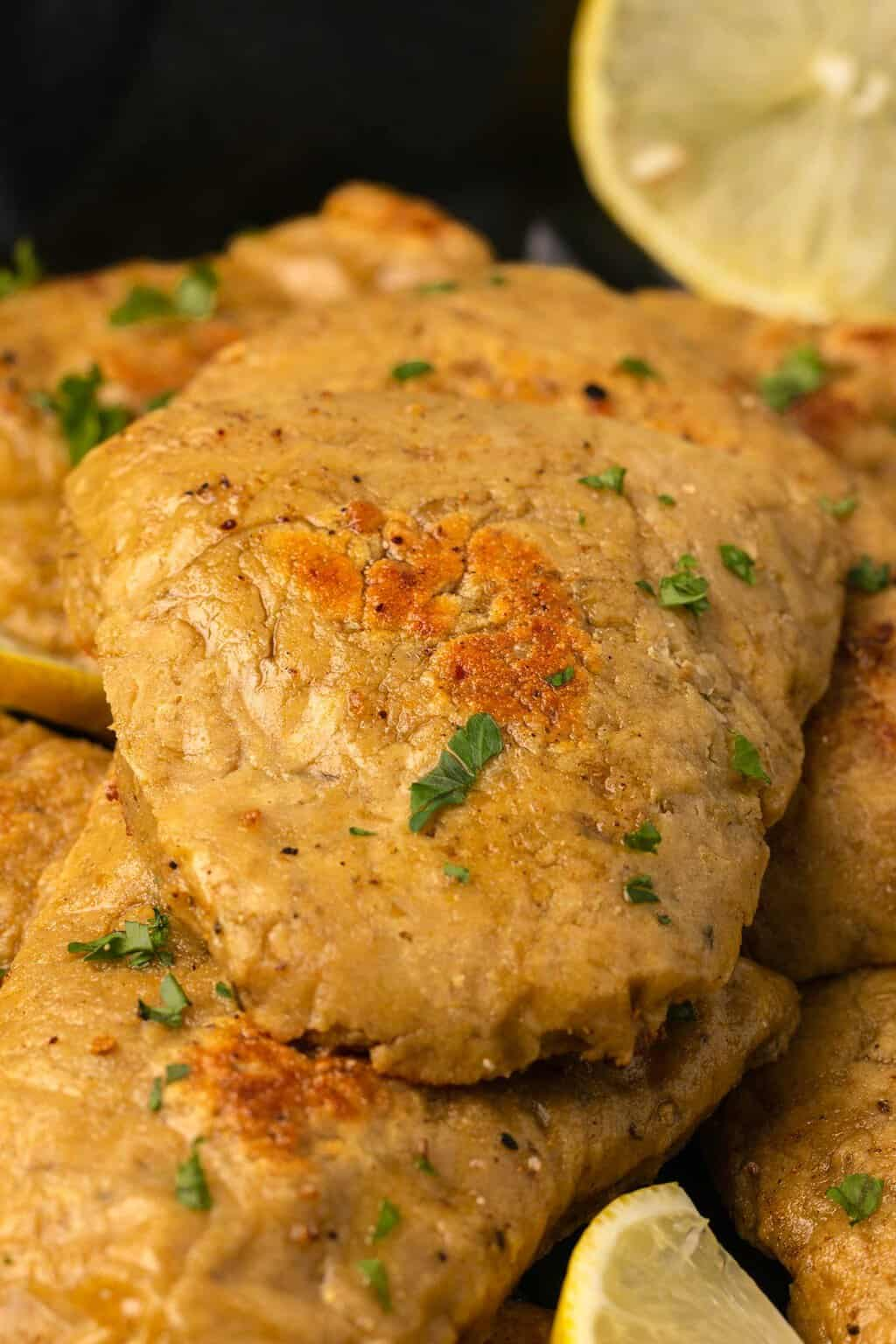 Vegan chicken fillets topped with chopped parsley.