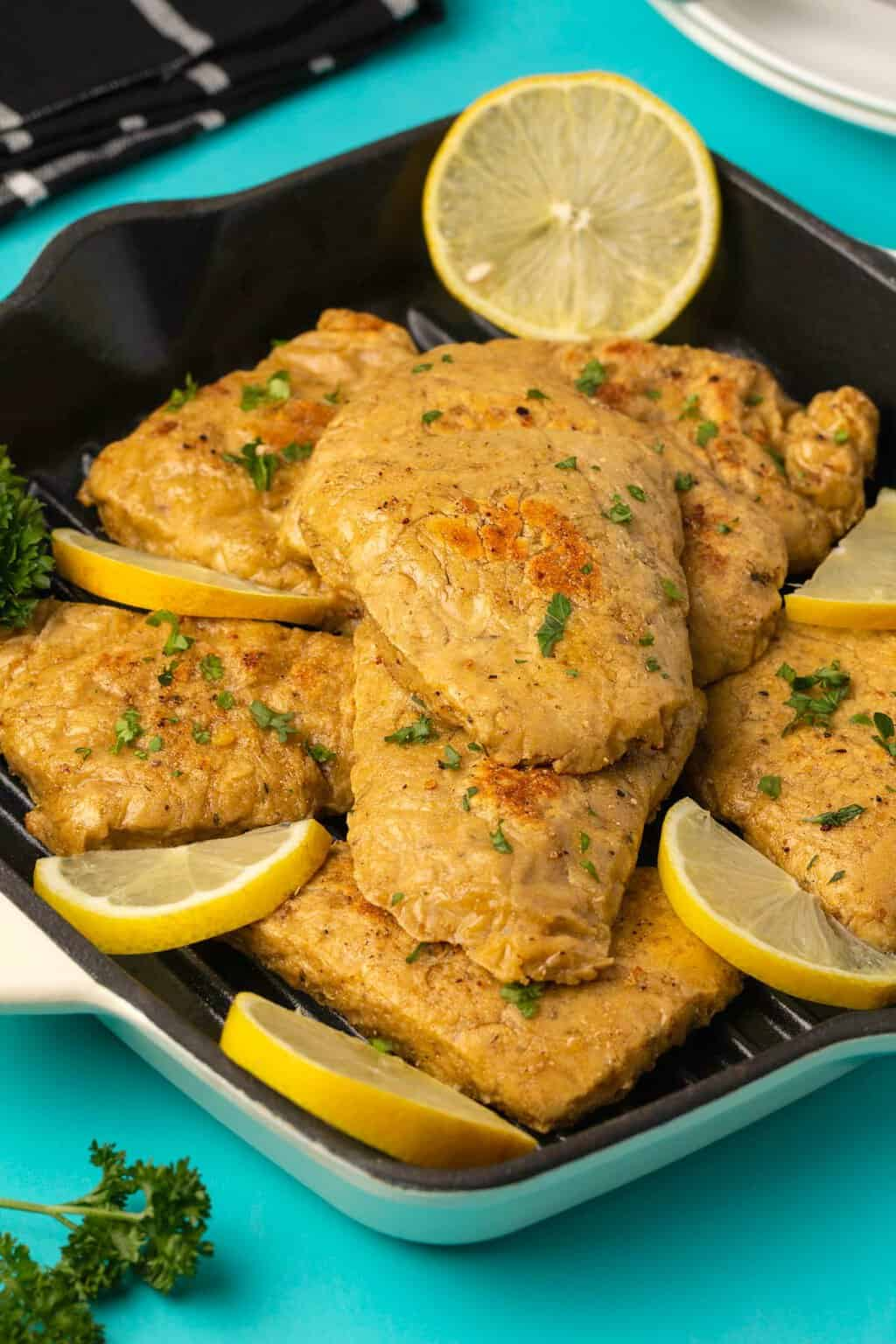 Vegan chicken fillets with chopped parsley and slices of lemon.