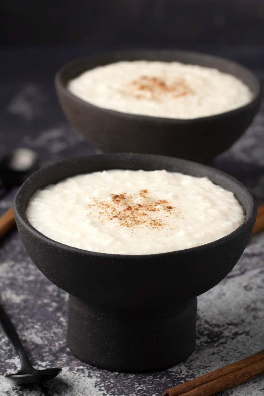 Vegan rice pudding topped with a sprinkle of cinnamon in black bowls.