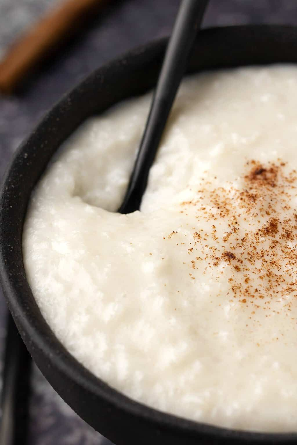 Vegan rice pudding in a black bowl with a spoon.
