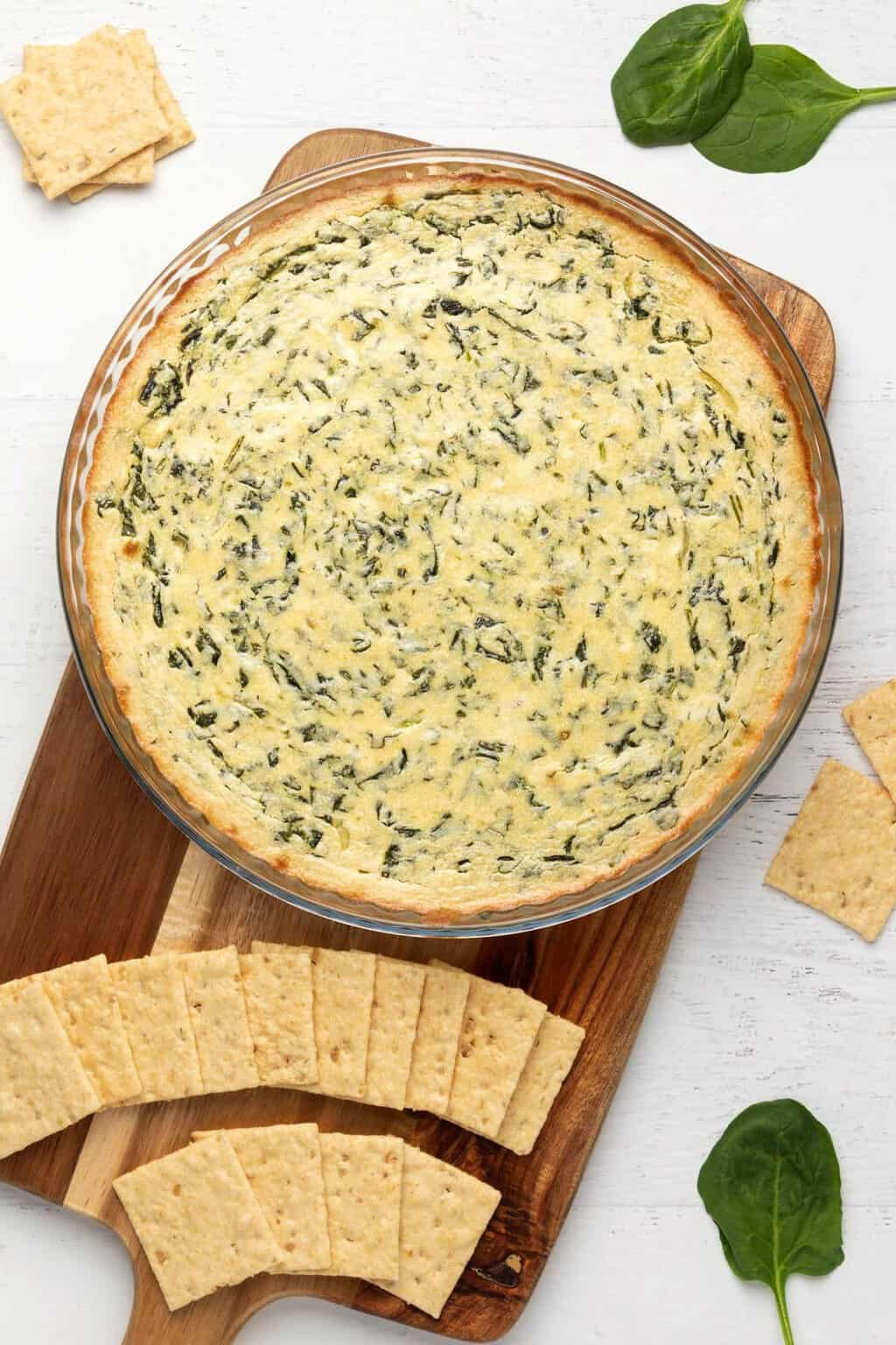 Freshly baked vegan spinach dip in a round glass dish.