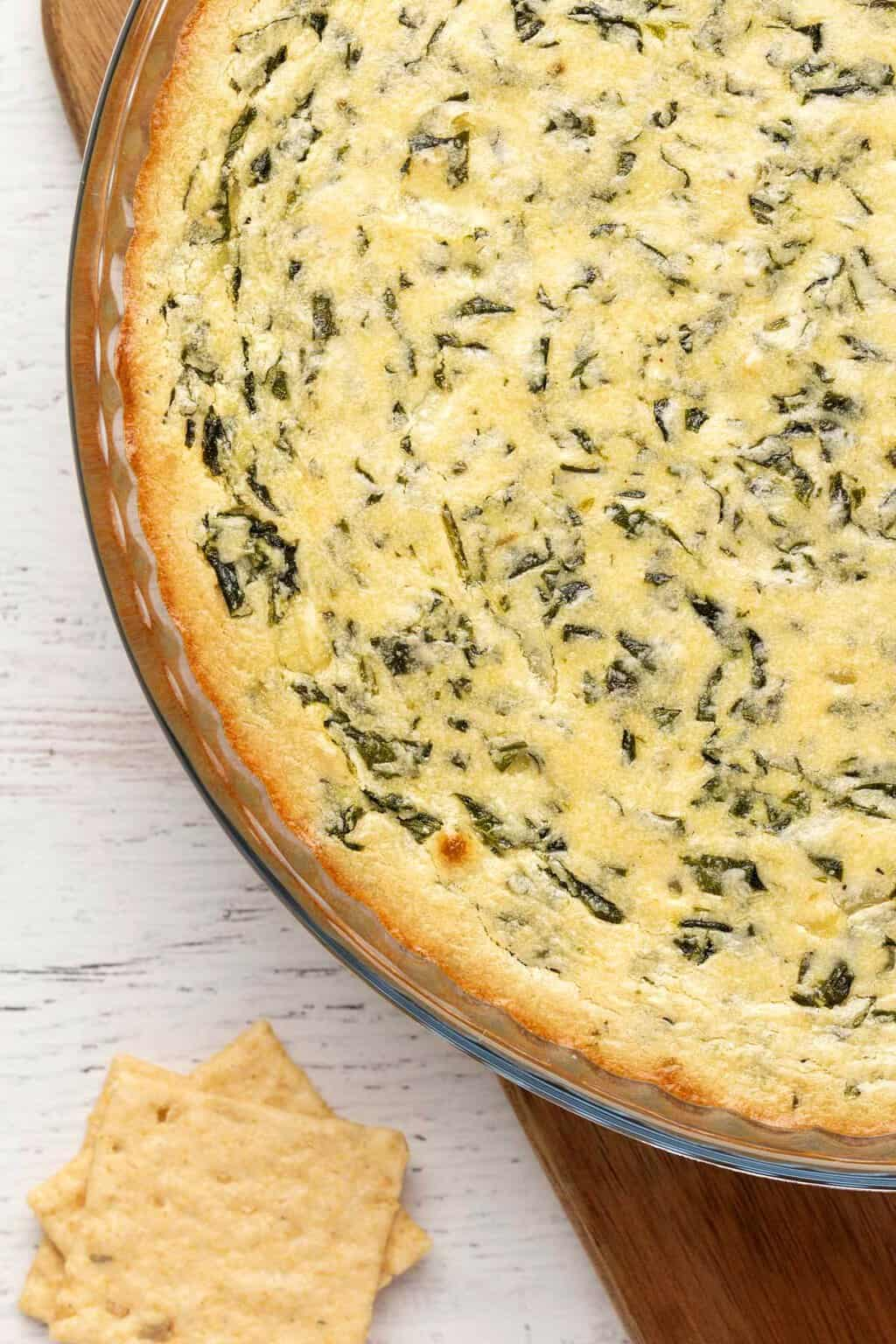 Vegan spinach dip in a round glass dish.