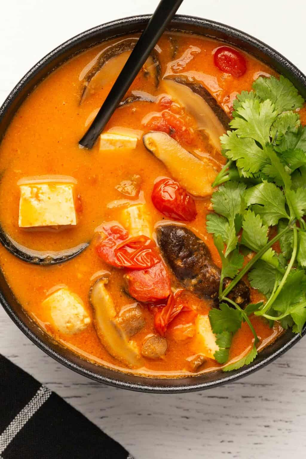 Vegan tom yum soup in a black bowl with a spoon.