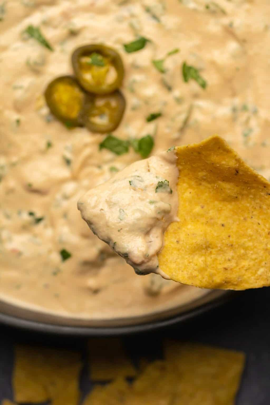 Cashew queso on a tortilla chip.