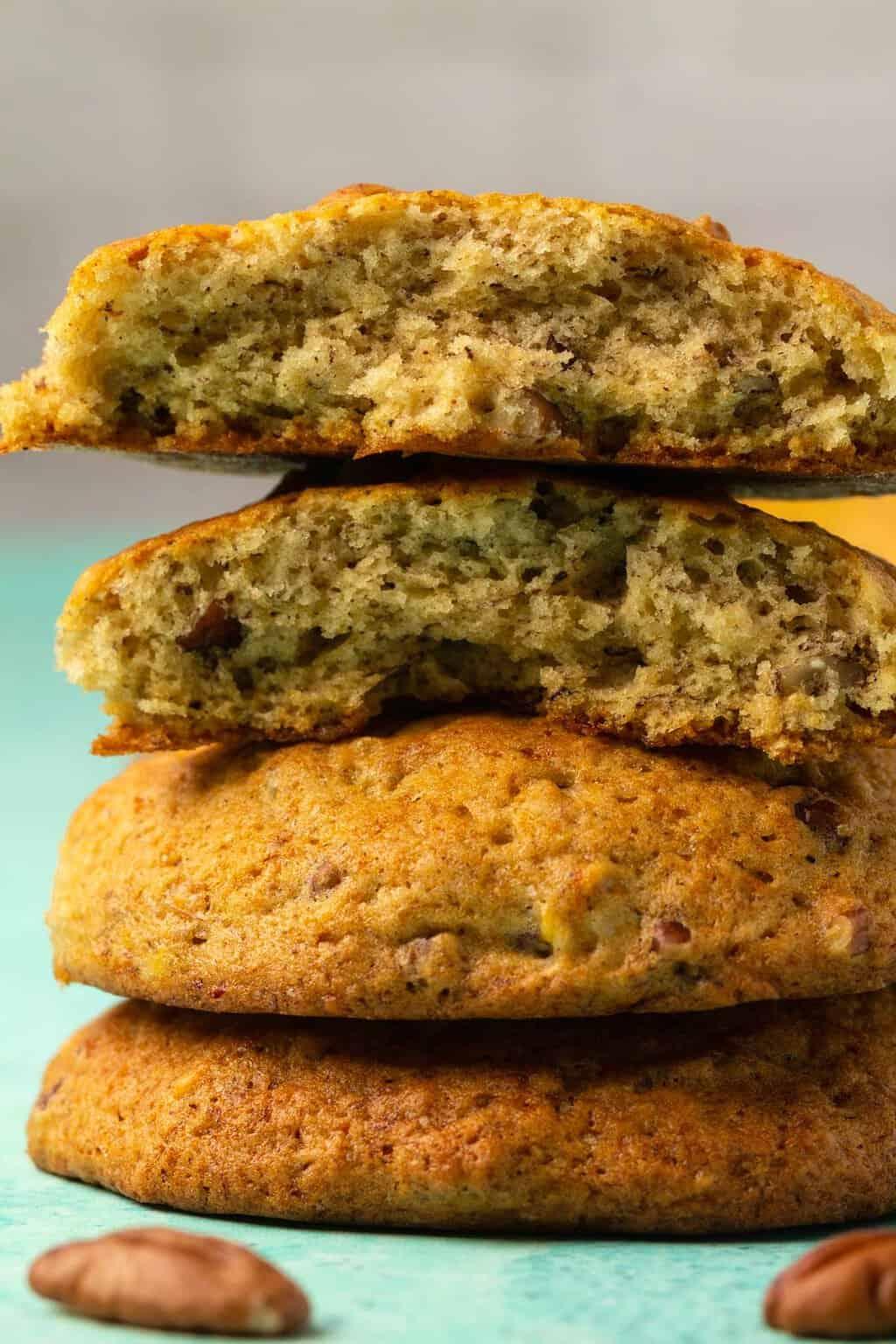 Vegan banana cookies in a stack with the top cookie broken in half.
