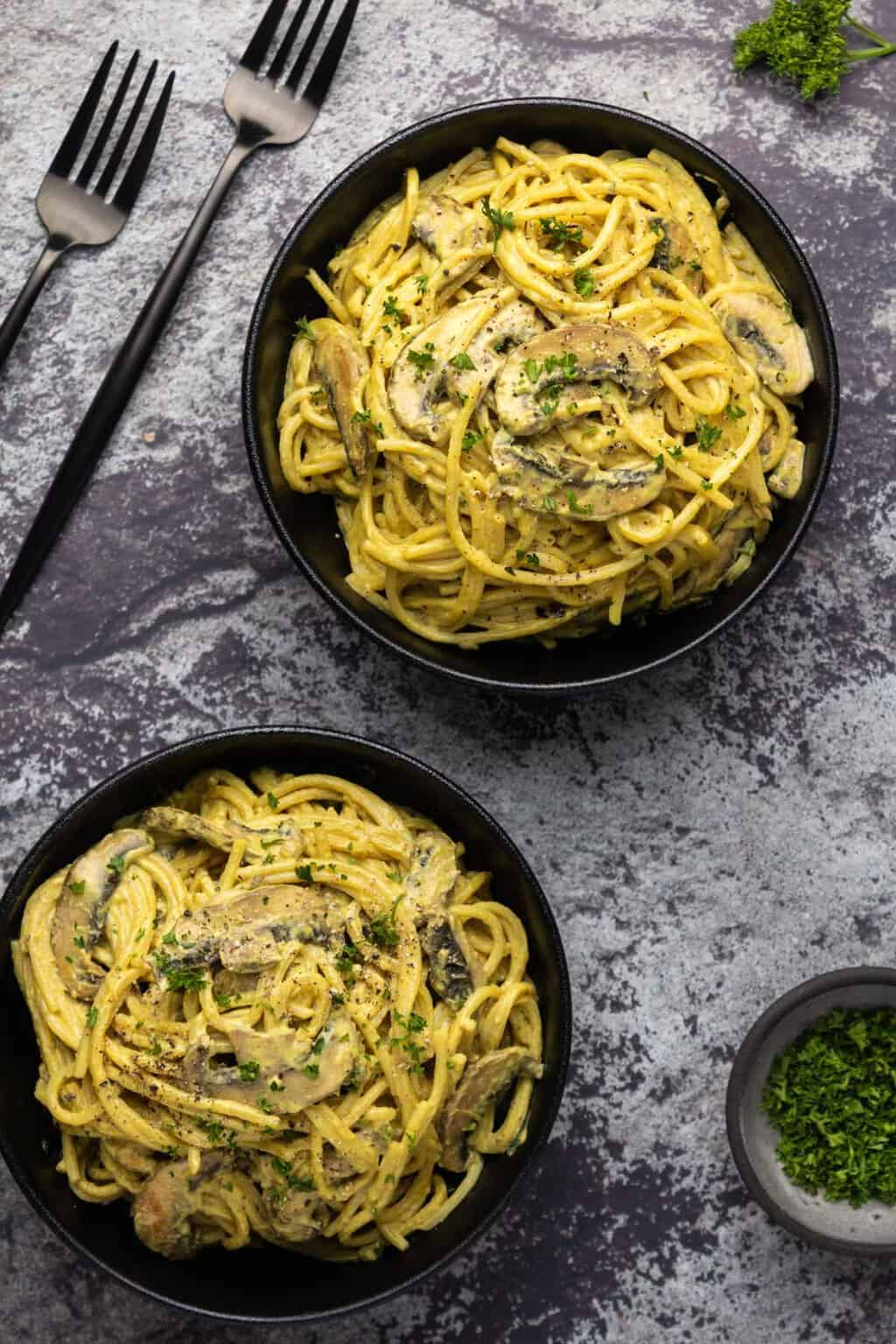 Vegan carbonara topped with chopped parsley in black bowls.