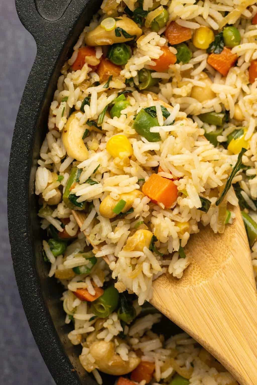 Vegan fried rice in a frying pan with a wooden spoon.