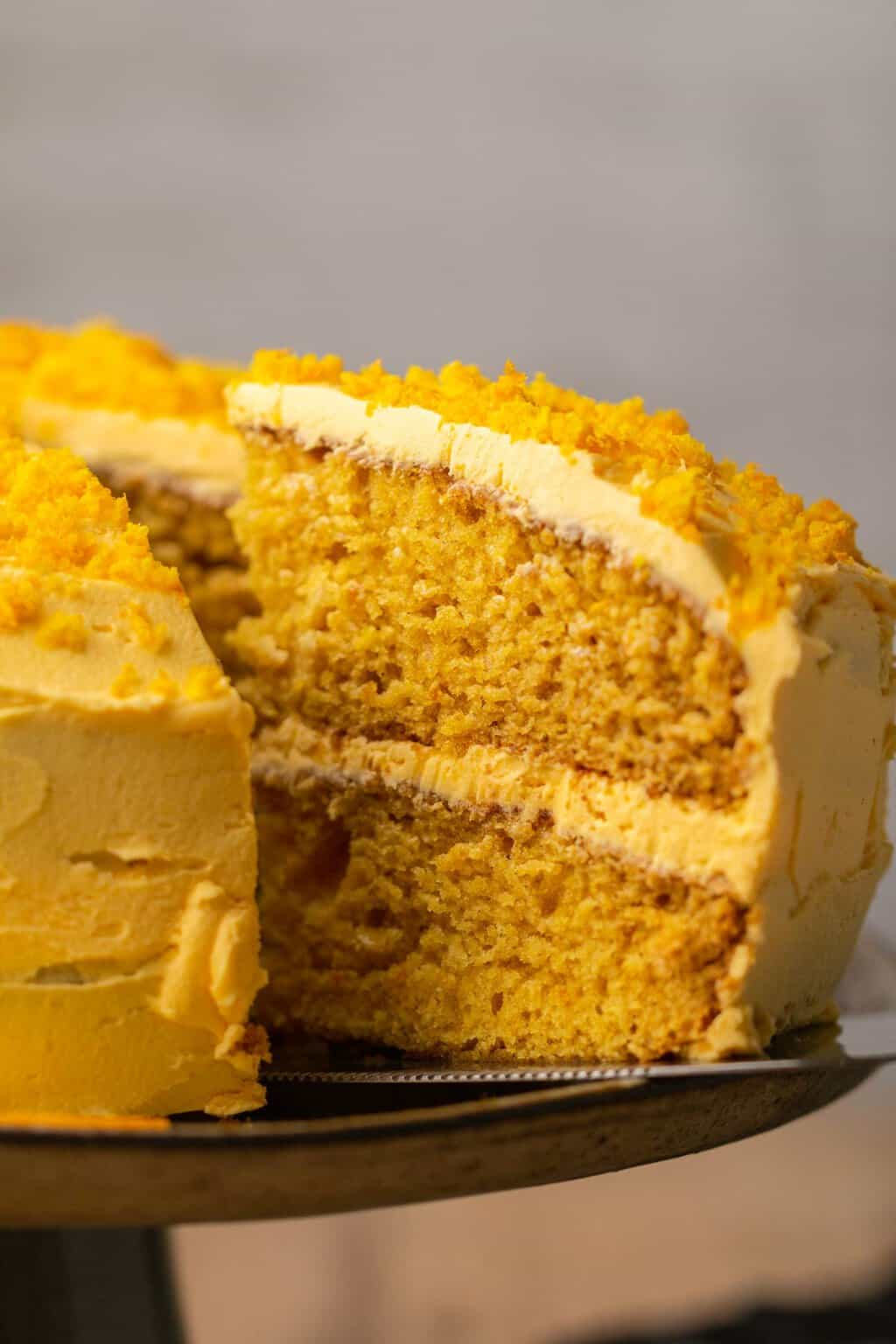 Sliced vegan orange cake with a cake lifter.