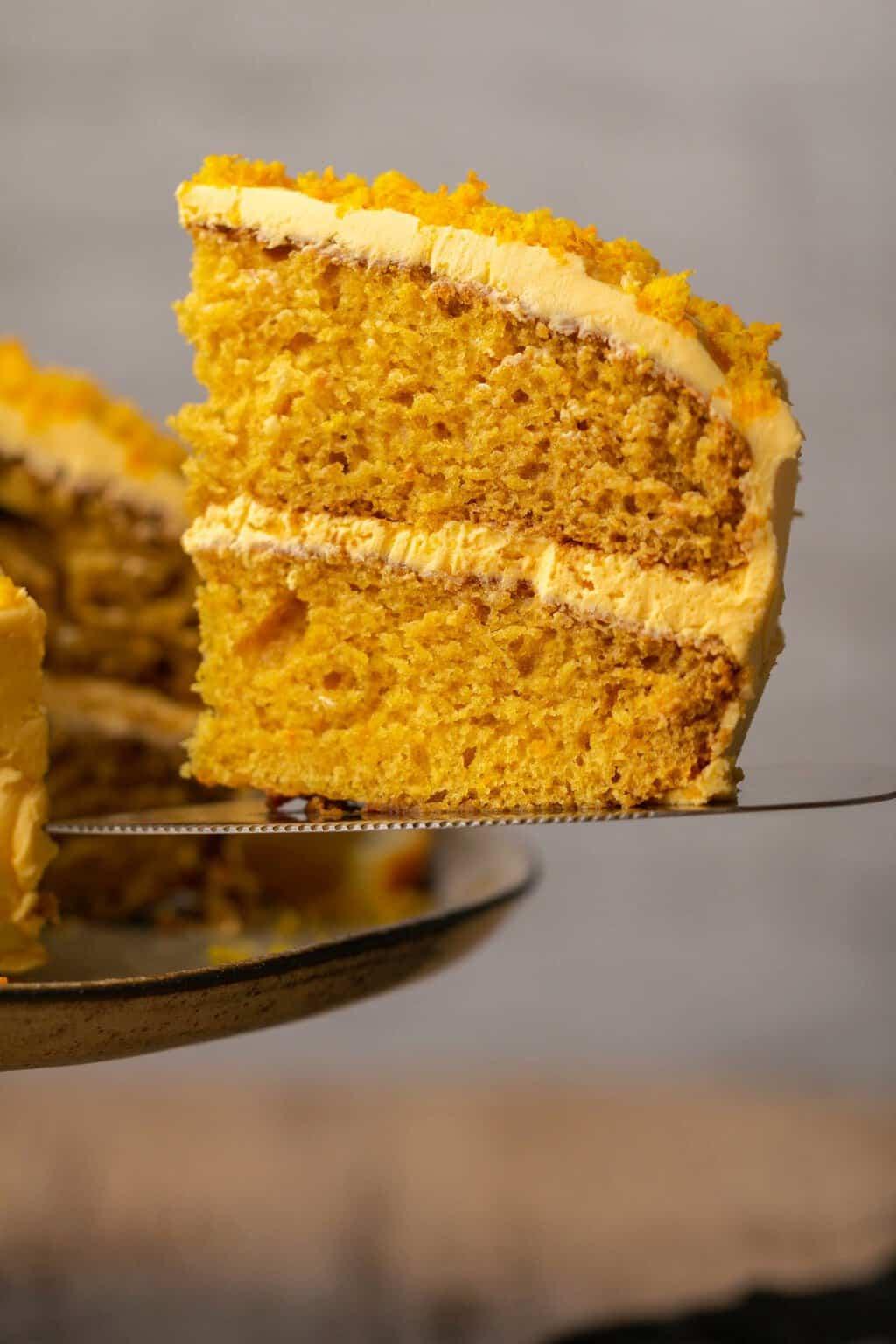 Slice of vegan orange cake on a cake lifter.