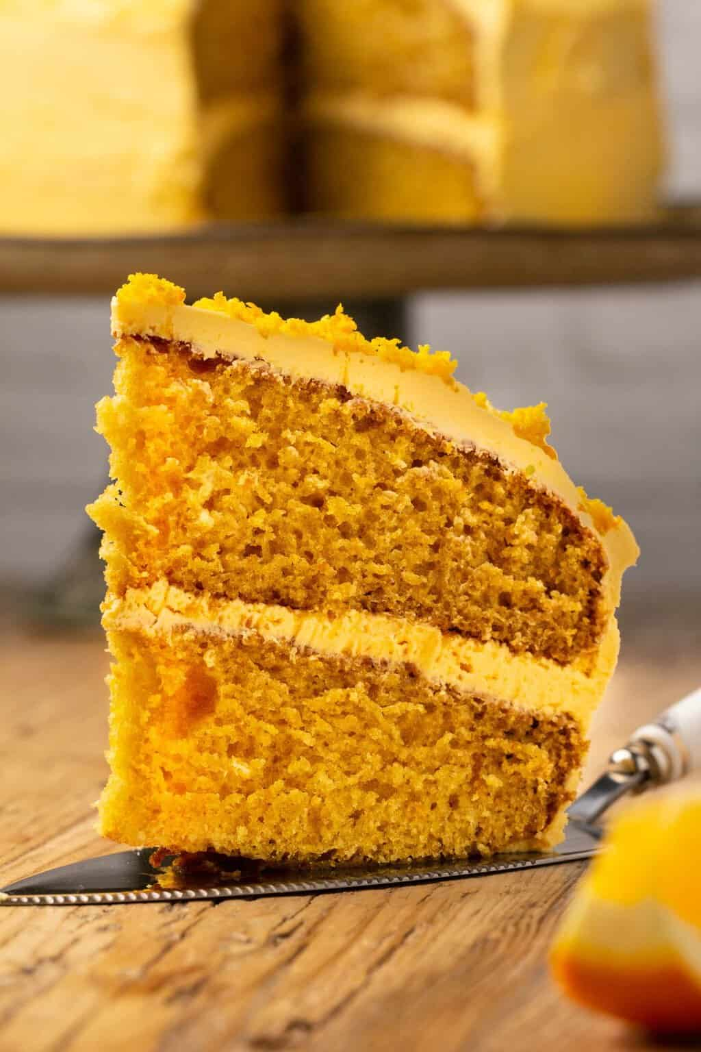 Slice of vegan orange cake on a cake lifter.