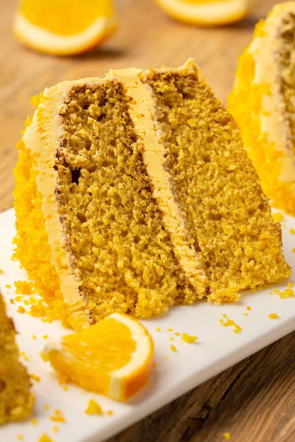 Slice of vegan orange cake on a white plate.