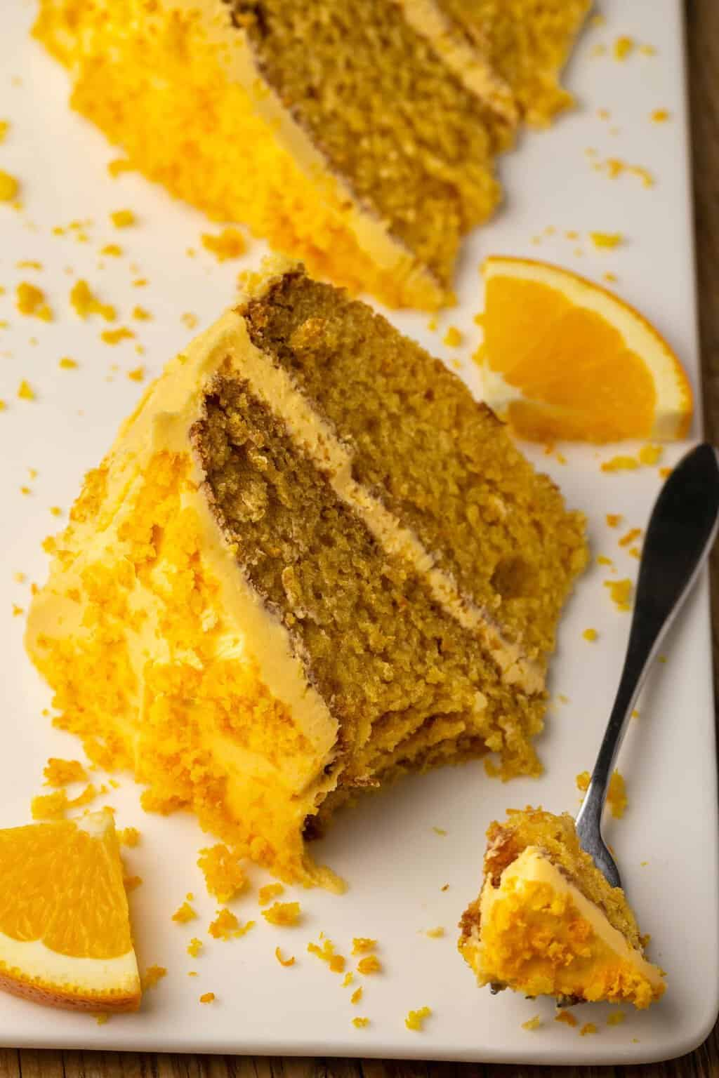 Slice of vegan orange cake on a white plate with a cake fork.