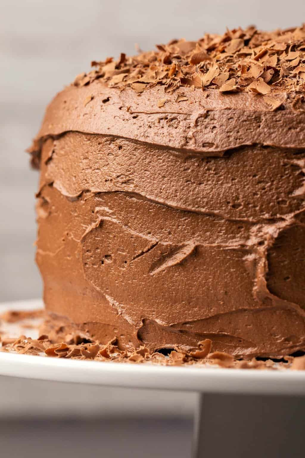 Vegan chocolate buttercream frosting spread onto a chocolate cake.