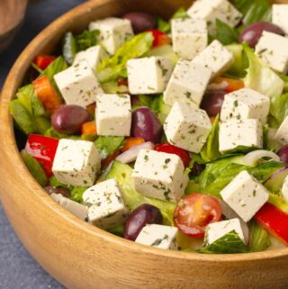 Vegan feta with salad in a wooden salad bowl