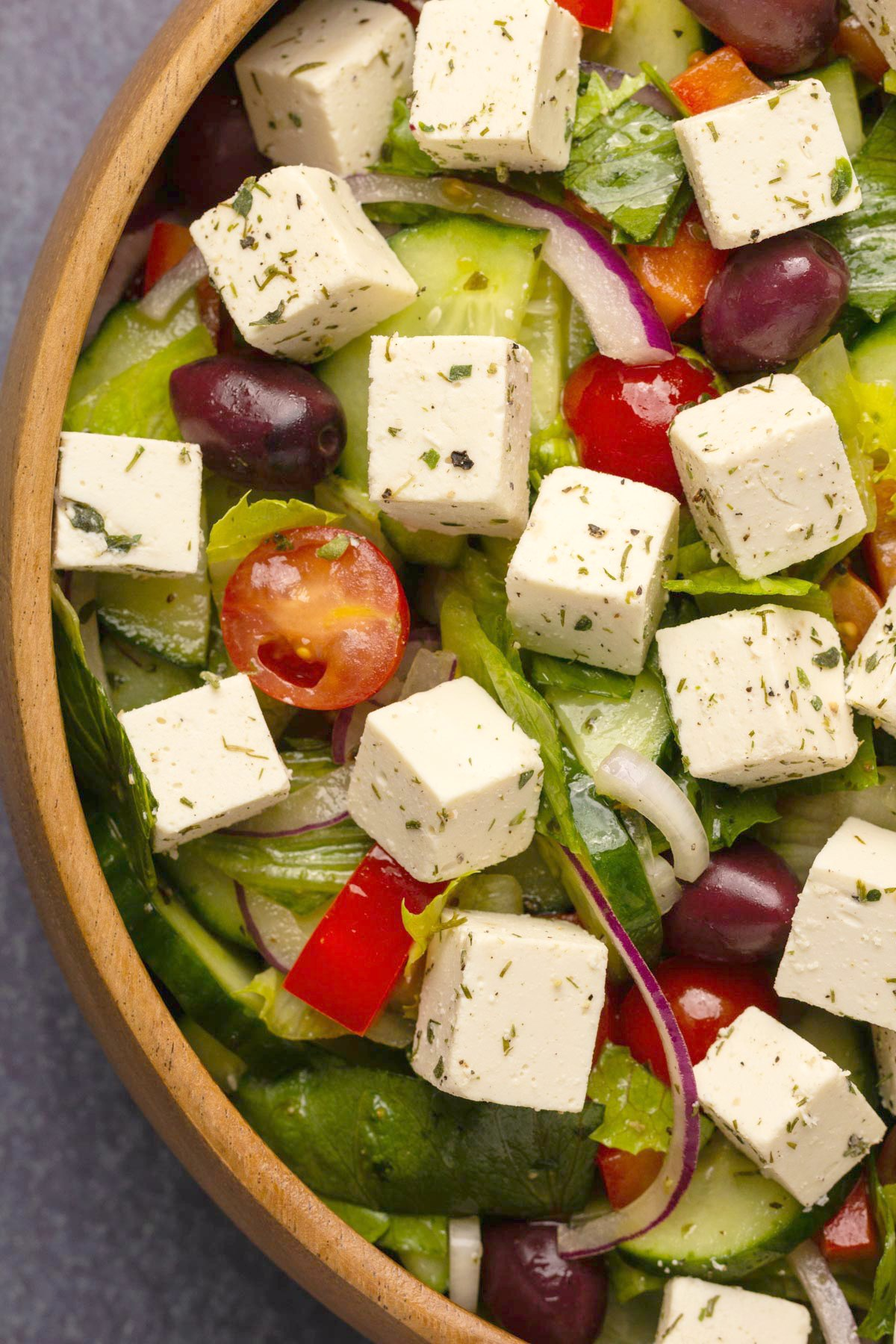 Vegan feta with oregano and dill on top of a Greek salad.