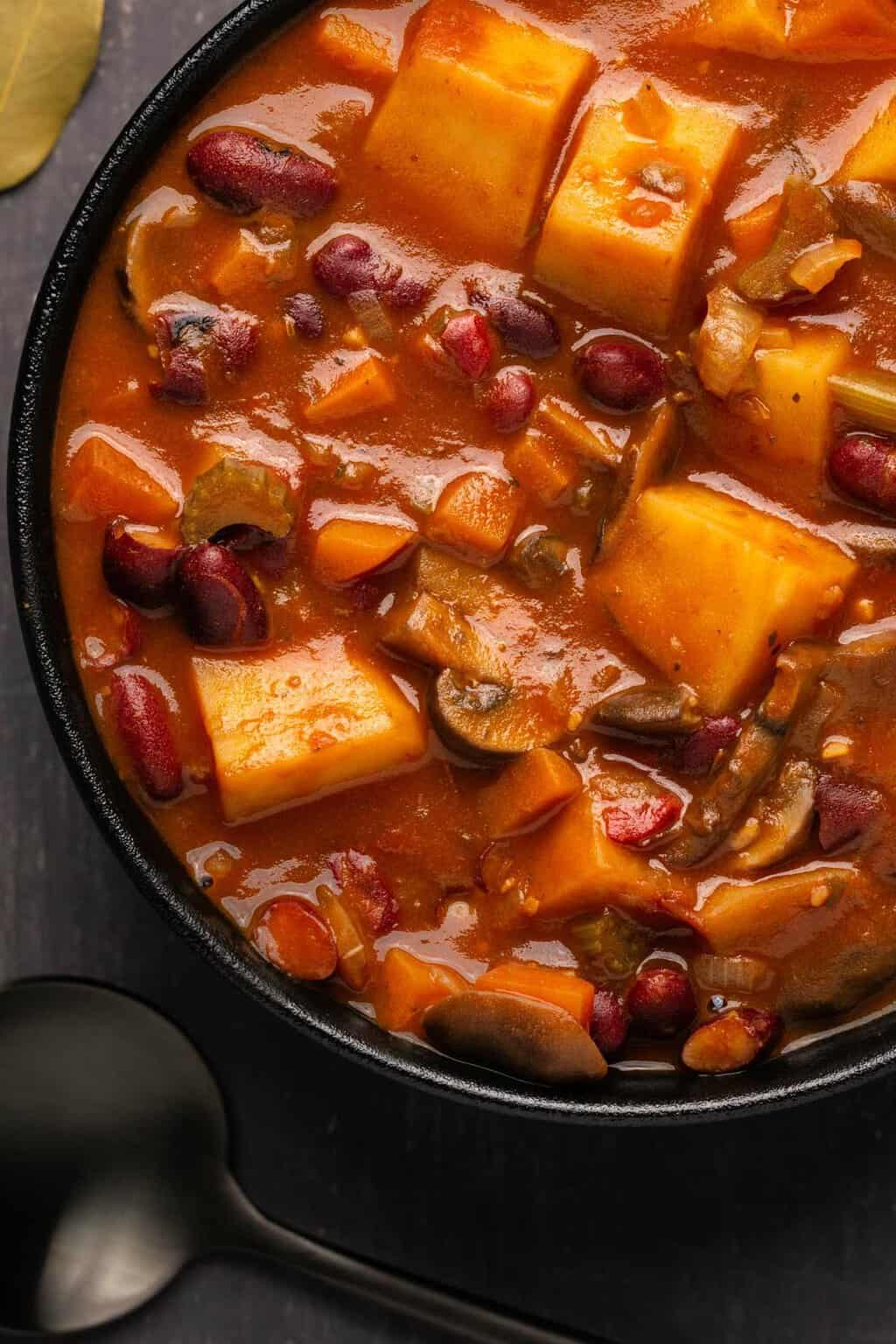Vegan stew in a black bowl.