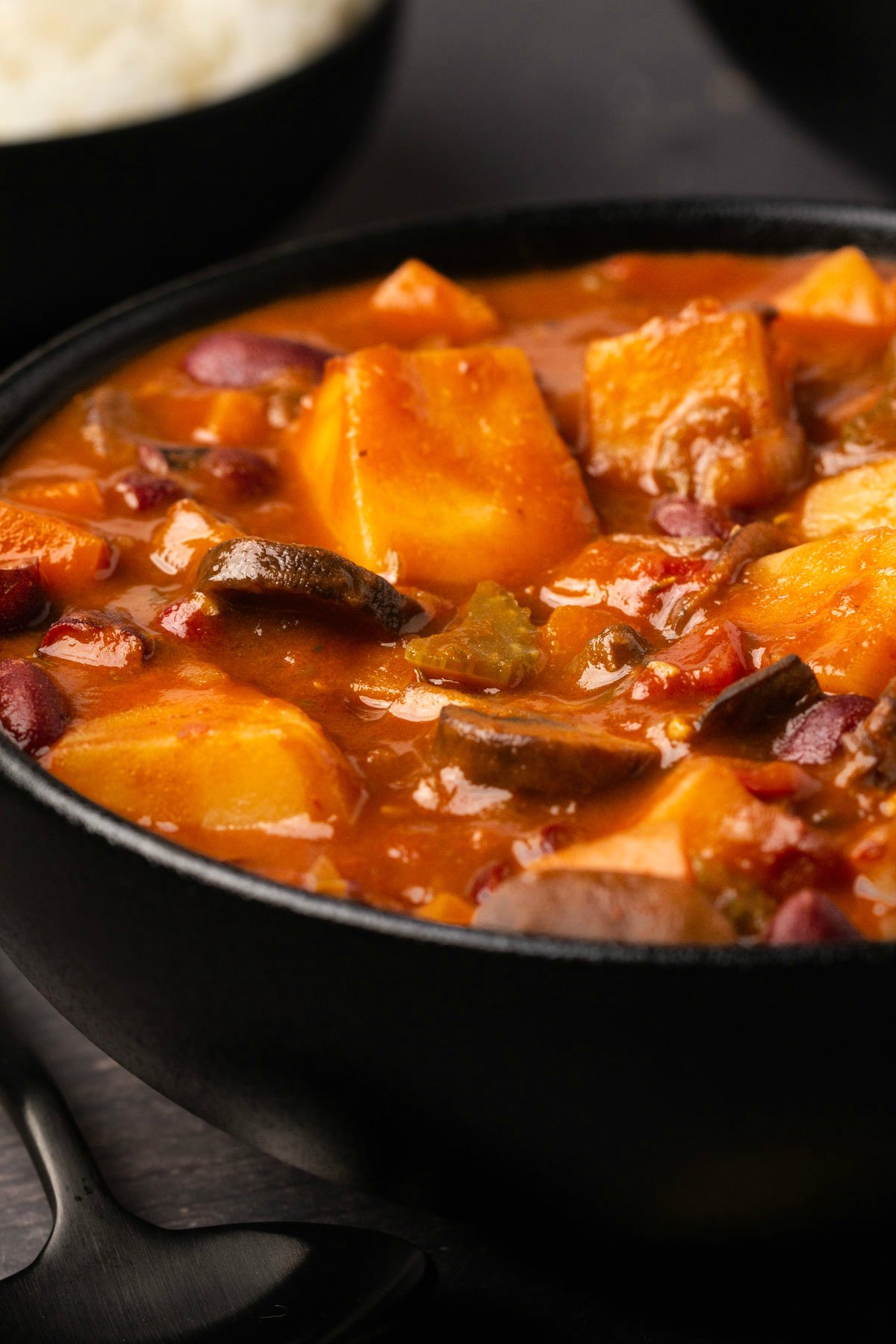 Vegan stew served in a black bowl.