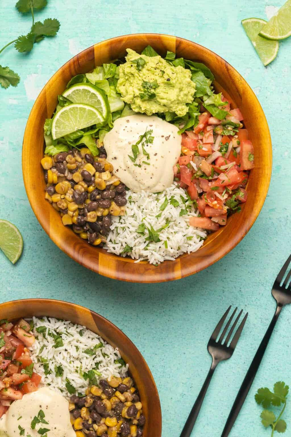 Vegan burrito bowls with cilantro lime rice, black beans and corn, pico de gallo, lettuce, guacamole and vegan sour cream.