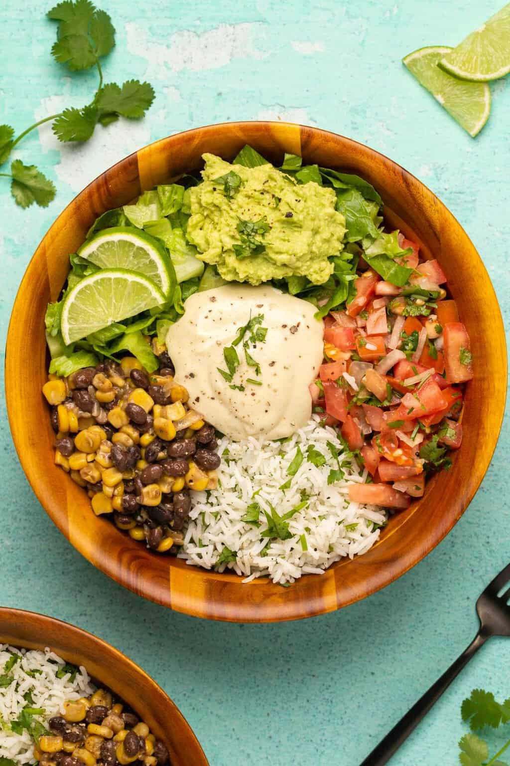 Vegan burrito bowls topped with chopped cilantro and fresh lime.