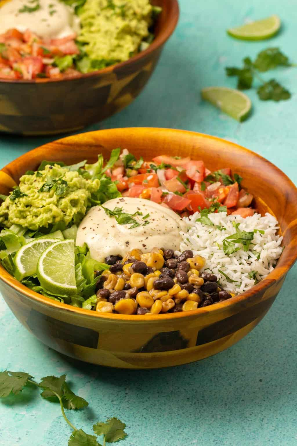 Vegan burrito bowls topped with chopped cilantro and fresh lime slices.