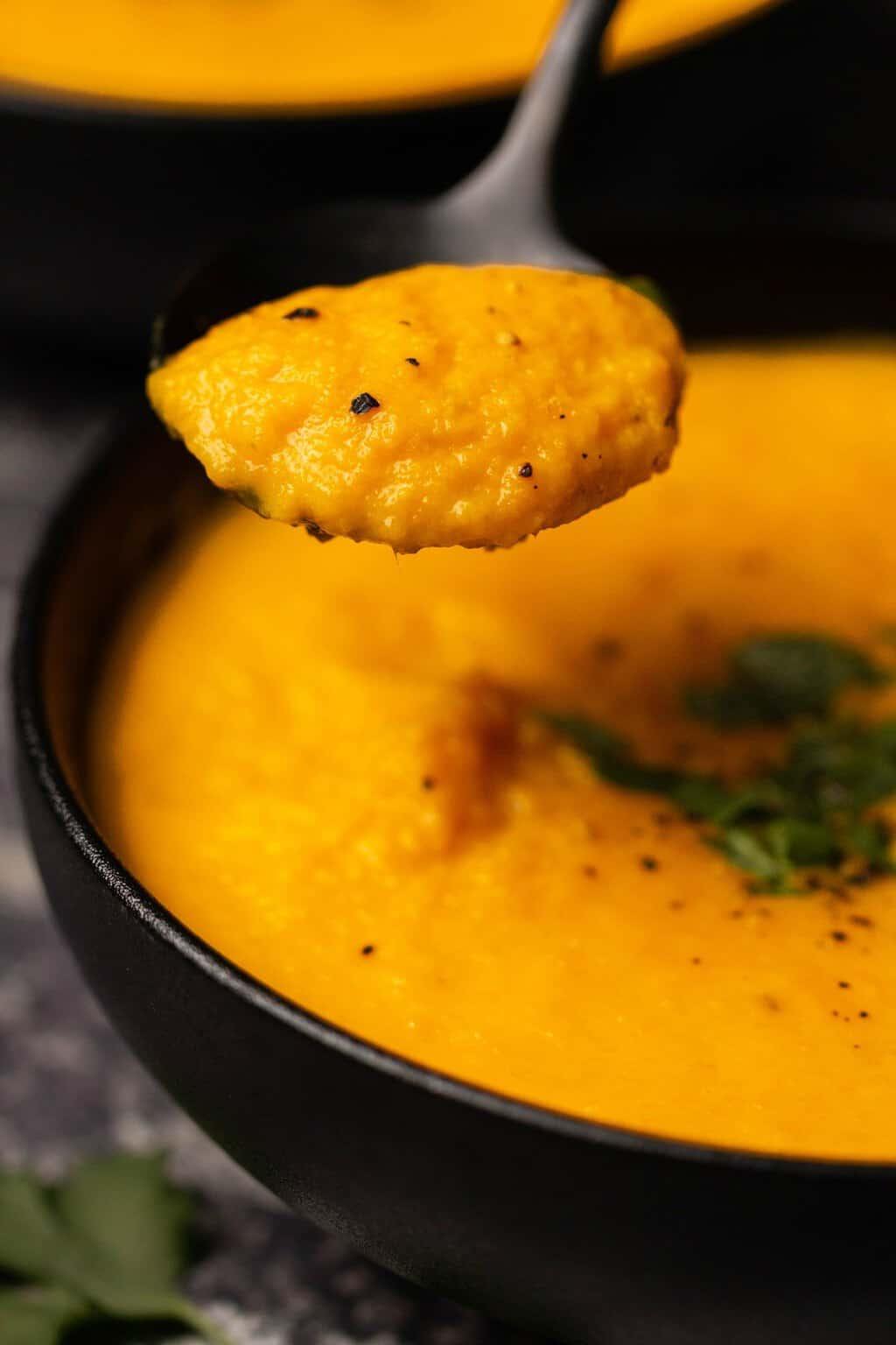 Spoonful of vegan carrot ginger soup.