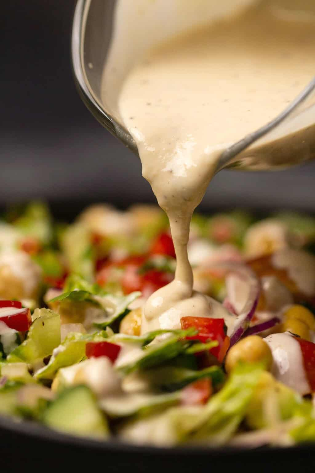 Tahini salad dressing pouring onto a bowl of chickpea salad.