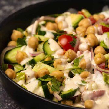 Vegan chickpea salad in a black bowl.