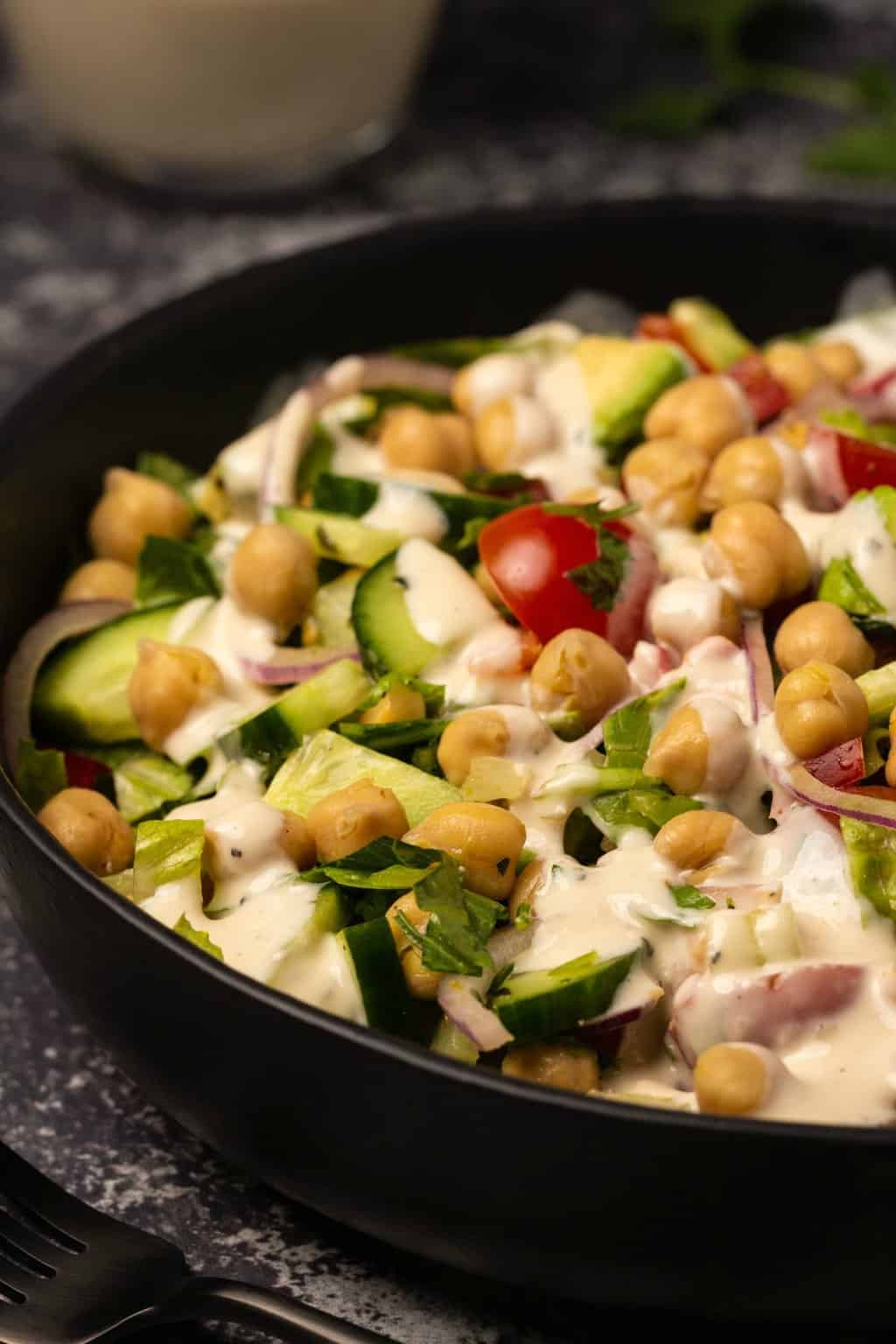 Vegan chickpea salad topped with tahini dressing in a black bowl.