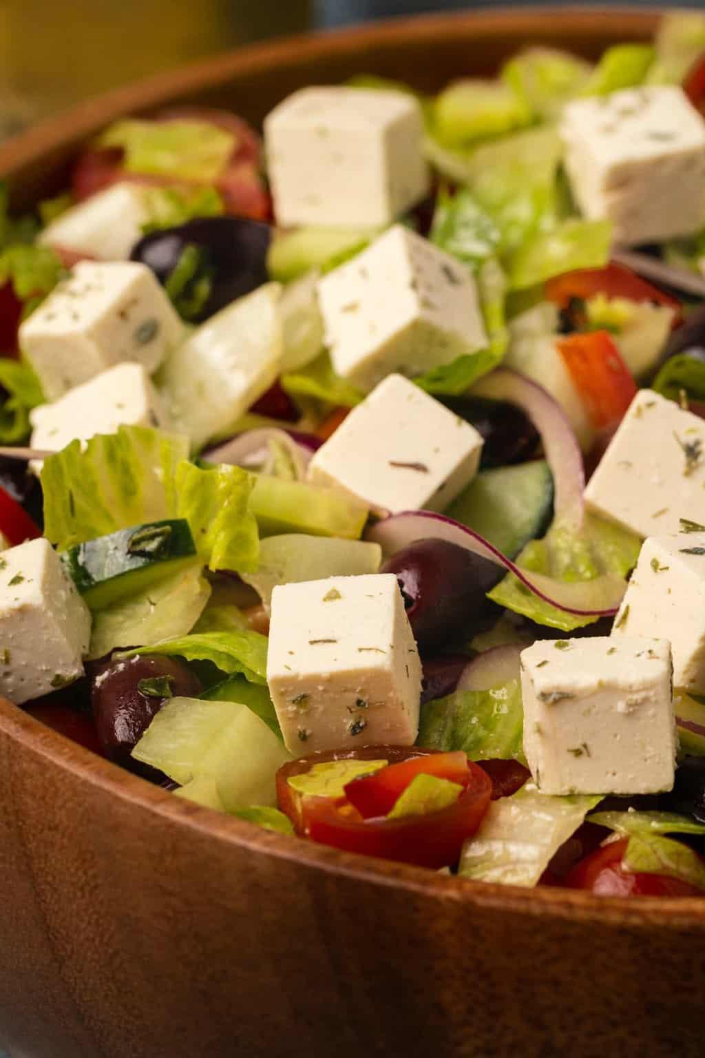 Vegan Greek Salad in a wooden salad bowl.