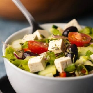 Vegan Greek salad in a white bowl with a fork.