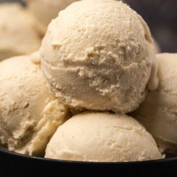 Scoops of vegan ice cream in a black bowl.