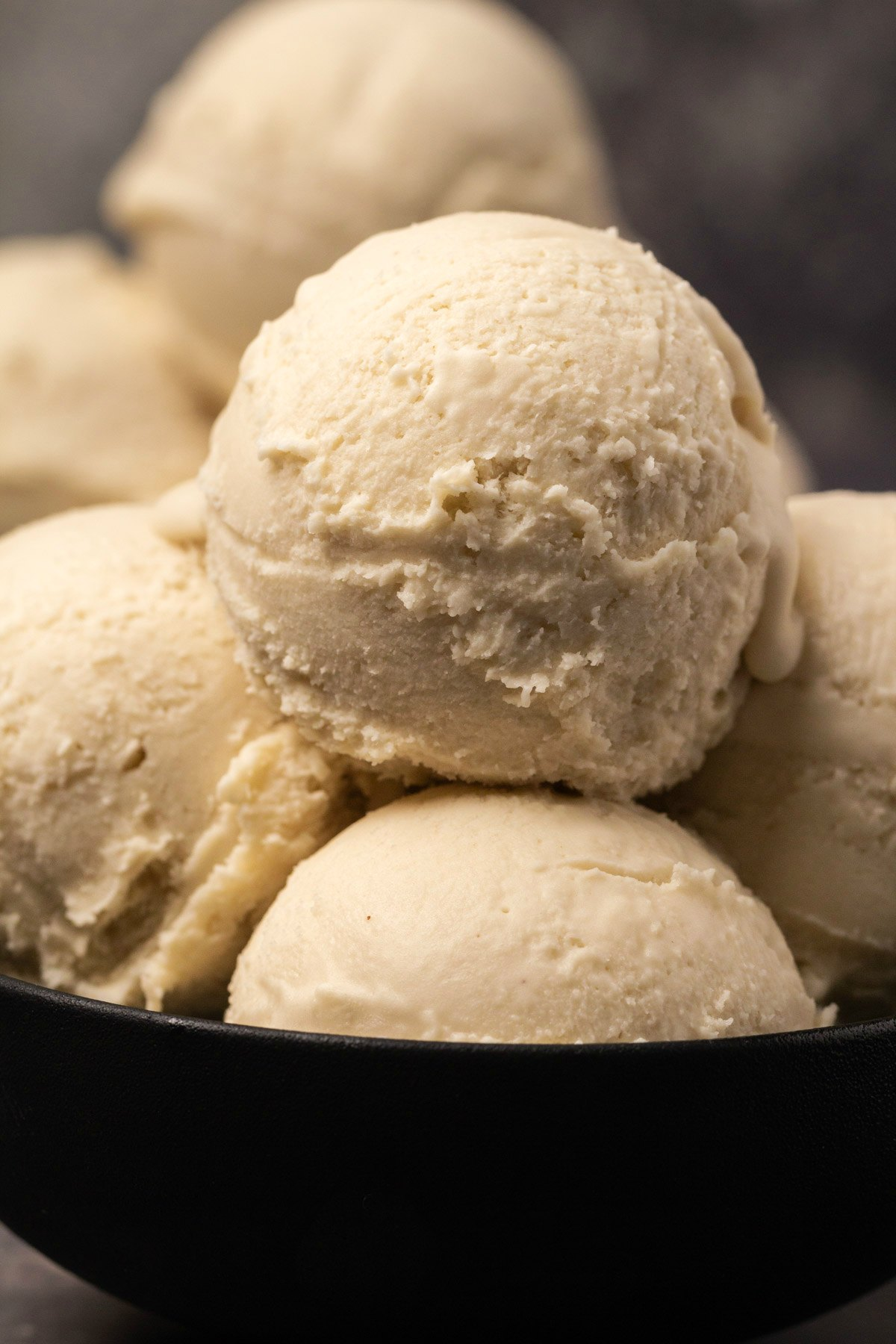 Vegan ice cream scoops in a black bowl.