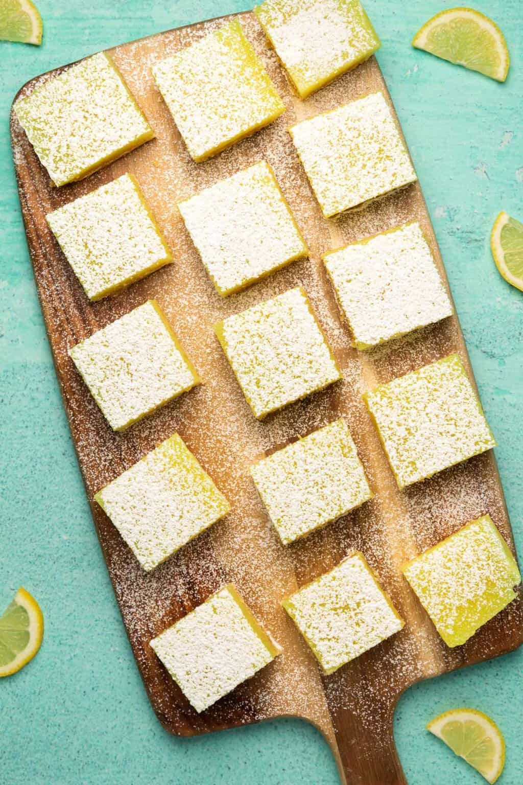Vegan lemon bars cut into squares on a wooden board.