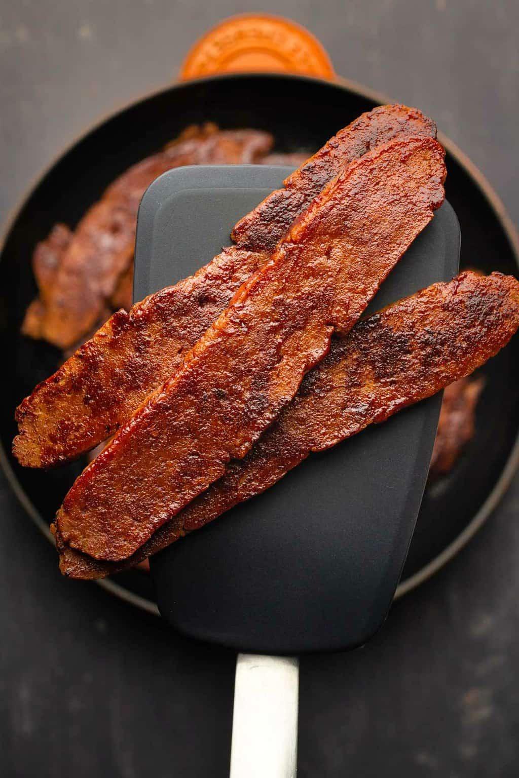 Vegan bacon strips on a spatula.