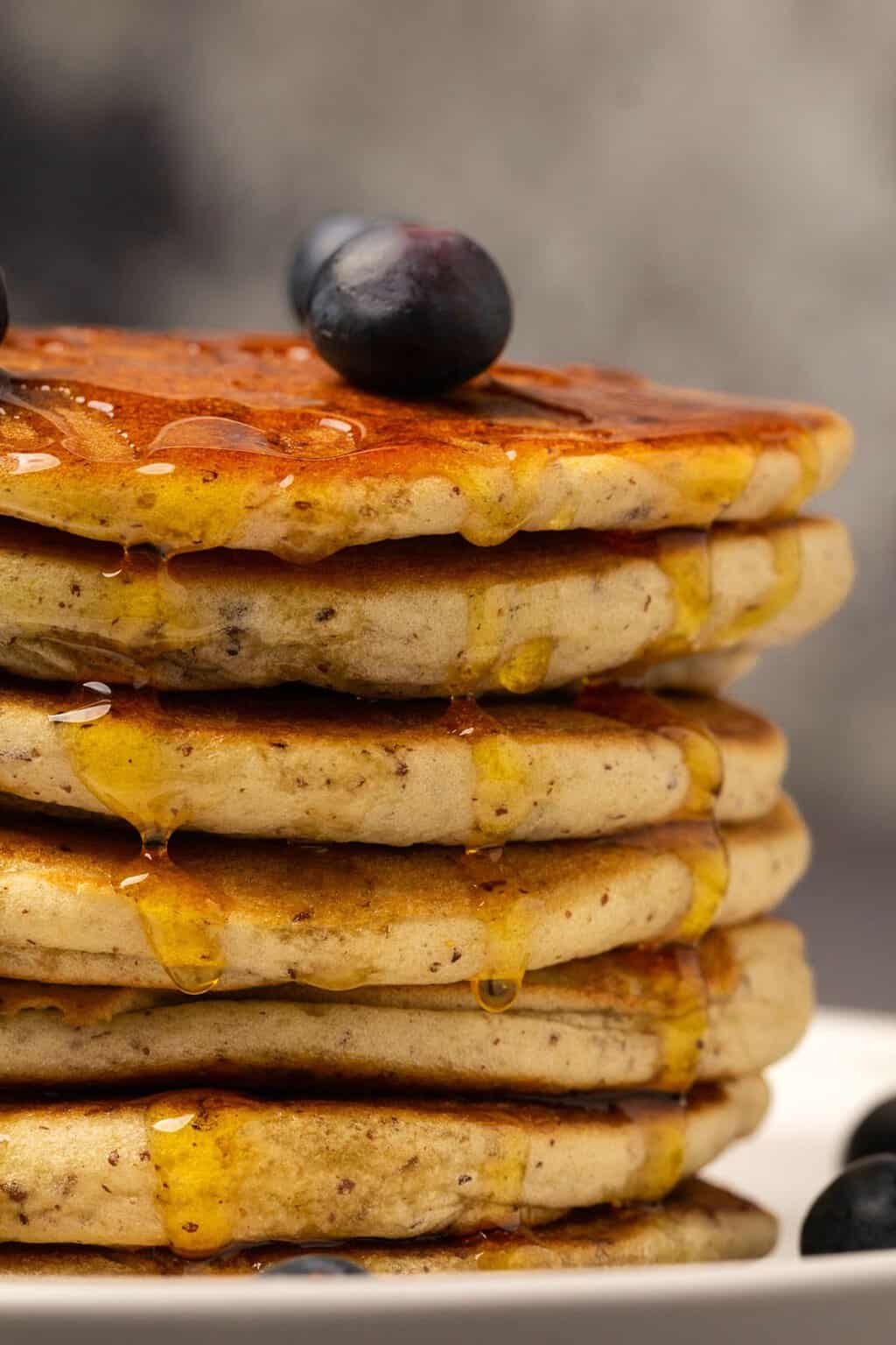 Vegan gluten free pancakes topped with syrup and fresh blueberries.